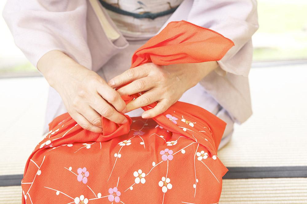 風呂敷で贈答品を包む女性の手